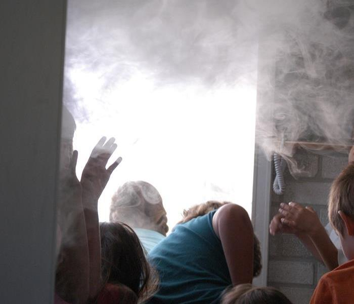 in this picture you will see children following fire safty practice when a room is filled with smoke.